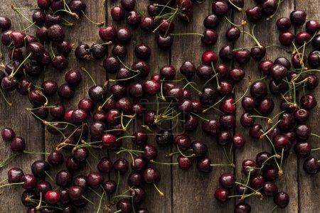 Draufsicht auf rote, frische, ganze und gewaschene Kirschen auf Holzoberfläche