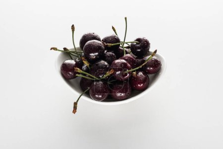 Photo for Red, whole and ripe cherries covered with water drops on bowl - Royalty Free Image