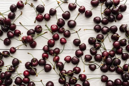 Photo for Top view of fresh, sweet and ripe cherries covered with droplets on wooden background - Royalty Free Image
