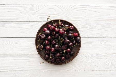 Draufsicht auf frische, süße und feuchte Kirschen auf Teller auf Holzgrund