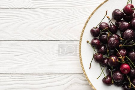 Photo for Top view of fresh, sweet and ripe cherries covered with droplets on white plate - Royalty Free Image