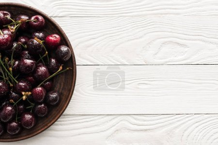 Photo for Top view of fresh, sweet and ripe cherries covered with droplets on plate - Royalty Free Image