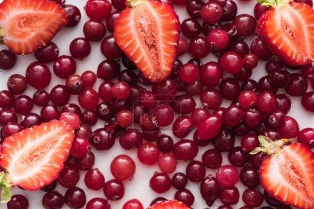 vue de dessus des canneberges rouges, fraîches et mûres, fraises coupées