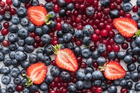 Photo for Top view of red, fresh and ripe cranberries, cut strawberries, blueberries - Royalty Free Image