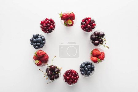 Photo for Top view of whole cranberries, whole strawberries, blueberries and cherries in plastic cups - Royalty Free Image