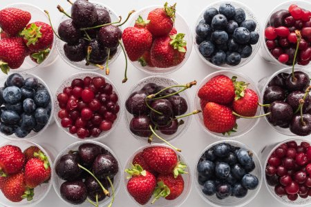 Photo for Top view of whole cranberries, fresh strawberries, blueberries and cherries in plastic cups - Royalty Free Image