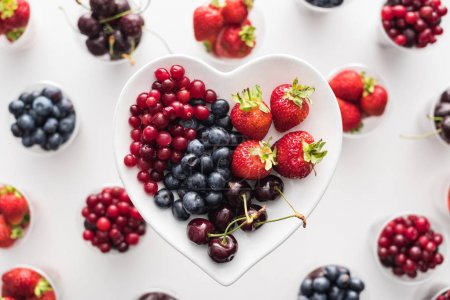 Photo for Top view of whole cranberries, strawberries, blueberries and cherries on heart shaped plate - Royalty Free Image