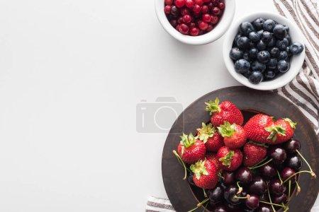 Photo pour Vue du haut des canneberges entières et des bleuets sur le bol, des fraises et des cerises sur l'assiette - image libre de droit