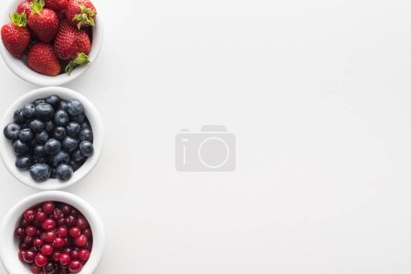 Photo for Top view of whole cranberries and blueberries, strawberries on bowls - Royalty Free Image