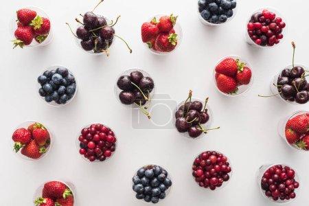 Photo pour Vue du haut des canneberges entières, des fraises fraîches, des bleuets et des cerises dans des tasses en plastique - image libre de droit