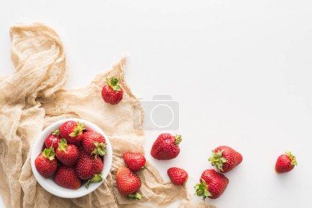 Photo pour Vue de dessus des fraises entières et rouges sur bol et tissu beige - image libre de droit