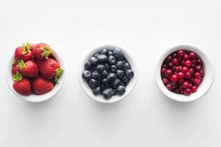 Photo for Top view of sweet cranberries and blueberries, strawberries on white bowls - Royalty Free Image