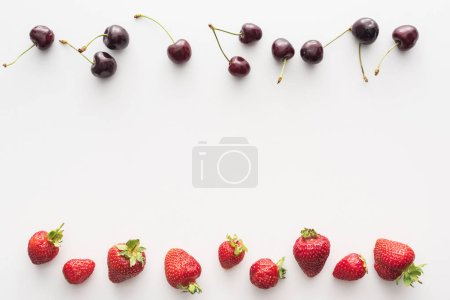Photo for Top view of sweet, fresh cherries and red strawberries on white background - Royalty Free Image
