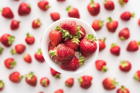 Photo for Top view of sweet  and red strawberries on white bowl - Royalty Free Image