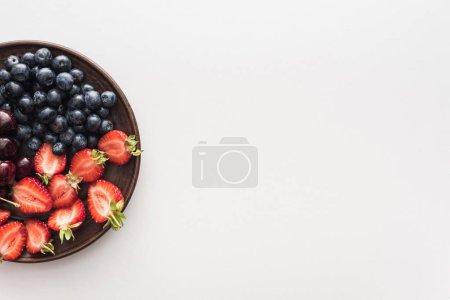Photo pour Vue du haut des bleuets doux, des cerises et des fraises coupées sur l'assiette - image libre de droit