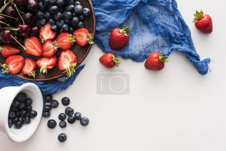 Photo for Top view of sweet blueberries on bowl, cherries and cut strawberries on plate with blue cloth - Royalty Free Image