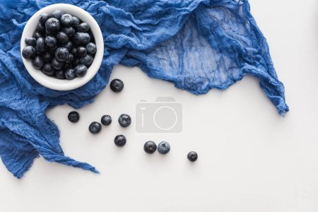 Photo for Top view of sweet blueberries on blue bowl with blue cloth - Royalty Free Image