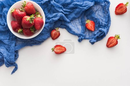 top view of sweet and red strawberries on bowl with blue cloth