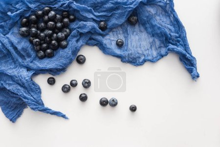 Photo for Top view of sweet and ripe blueberries on blue cloth - Royalty Free Image