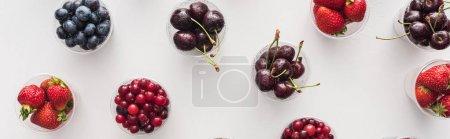 Foto de Foto panorámica de fresas frescas, arándanos, cerezas y arándanos en tazas de plástico - Imagen libre de derechos