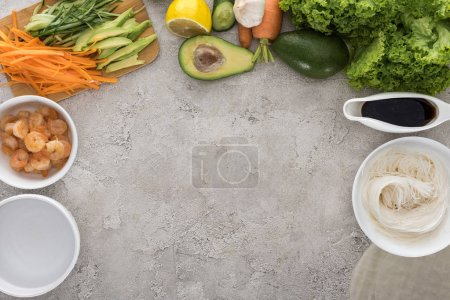 Foto de Top view of lemon, avocados, carrots, black pepper, shrimps, soy sauce, rice paper, garlic,noodles, sliced vegetables and lettuce on table - Imagen libre de derechos