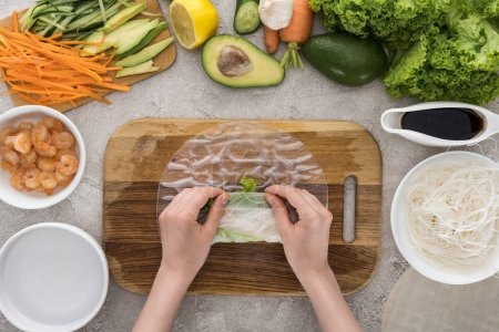 Photo for Top view of woman making roll on cutting board among ingredients - Royalty Free Image