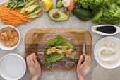 """Постер, картина, фотообои """"top view of woman making roll on cutting board with lettuce, shrimps and avocado """""""