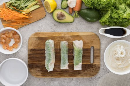 Photo for Top view of spring rolls on cutting board among ingredients - Royalty Free Image