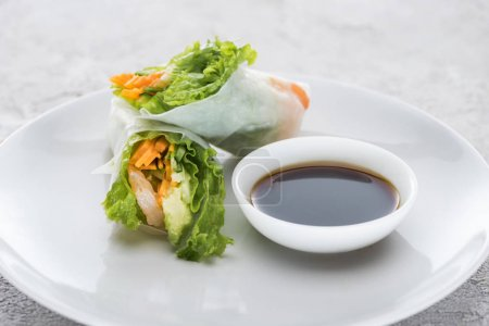 Photo for Tasty and served spring rolls with soy sauce on white plate - Royalty Free Image