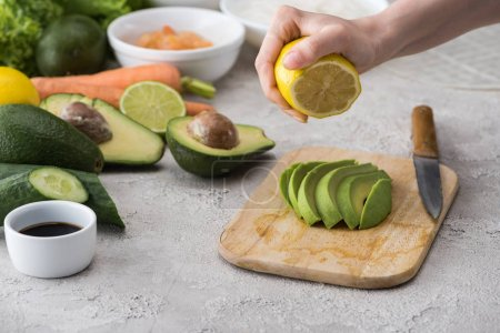 Photo for Cropped view of woman squeezing lemon on cut avocado on cutting board - Royalty Free Image
