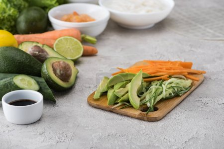 Photo for Cut avocado, carrot and cucumber on cutting board among raw ingredients - Royalty Free Image