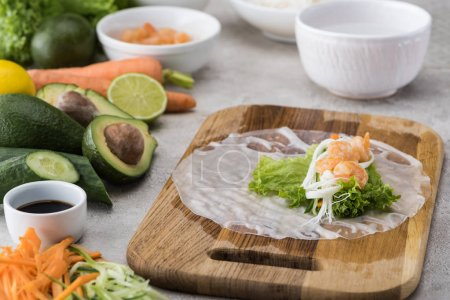 Photo for Lettuce, noodles  and shrimps on rice paper, on cutting board - Royalty Free Image