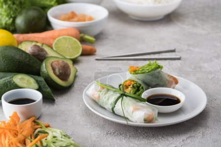 Tasty spring rolls with soy sauce on white plate w...