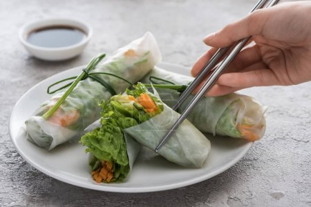 Photo for Cropped view of woman eating tasty spring rolls with metal sticks - Royalty Free Image