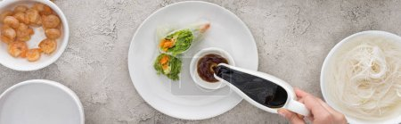 Photo for Panoramic shot of woman pouring soy sauce and tasty spring rolls on white plate - Royalty Free Image