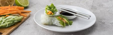 Photo for Panoramic shot of tasty and served spring rolls with soy sauce on white plate with metal sticks - Royalty Free Image