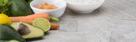Photo for Panoramic shot of lime, avocados, carrots, shrimps, rice paper, noodles on table - Royalty Free Image