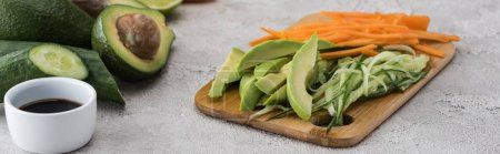 Photo for Panoramic shot of cut avocado, carrot and cucumber on cutting board - Royalty Free Image
