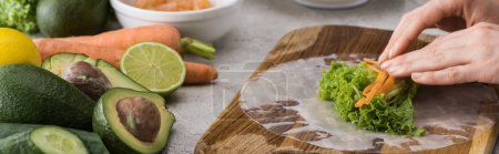 Photo for Panoramic shot of woman putting cut carrot on lettuce, on cutting board - Royalty Free Image