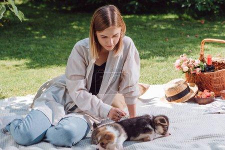 Foto de Rubia hermosa chica sentada en la manta blanca en el jardín y tener picnic en el día soleado con cachorros lindos - Imagen libre de derechos
