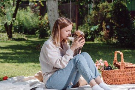 Foto de Tierna chica rubia sentada en manta blanca en el jardín con lindo cachorro corgi galés - Imagen libre de derechos