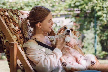 Photo for Cheerful blonde girl holding welsh corgi dog while sitting in deck chair in garden - Royalty Free Image