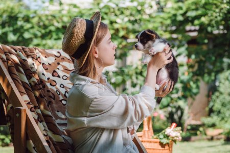Photo for Side view of blonde girl in straw hat holding puppy while sitting in deck chair in garden - Royalty Free Image