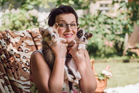 happy brunette middle aged woman holding welsh corgi puppies while sitting in deck chair in garden