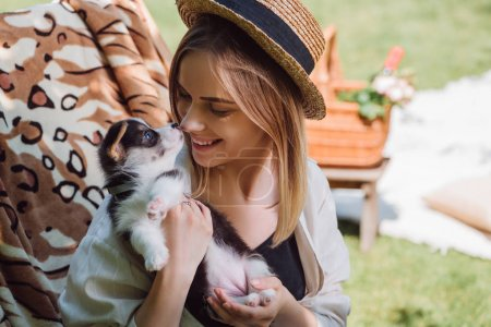 Photo for Happy blonde girl in straw hat looking at puppy while sitting in deck chair in garden - Royalty Free Image