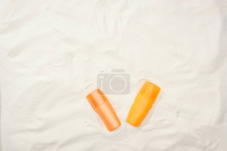 Photo for Orange bottles of sunscreen on sand with copy space - Royalty Free Image