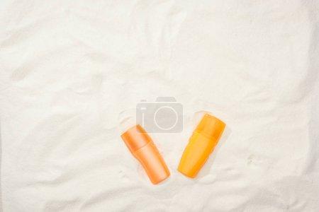 Photo pour Bouteilles orange de crème solaire sur sable avec espace de copie - image libre de droit
