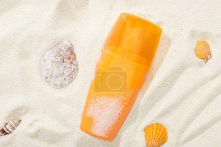 Photo pour Bouteille orange de protection solaire sur le sable avec des coquillages - image libre de droit