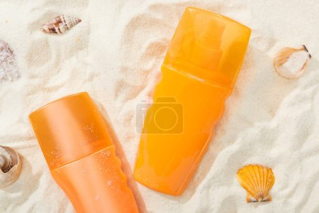 Photo for Orange bottles of sunscreen on golden sand with seashells - Royalty Free Image