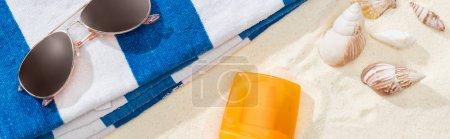 Photo pour Bouteille orange de protection solaire sur le sable avec des coquillages, serviette rayée et lunettes de soleil, projectile panoramique - image libre de droit